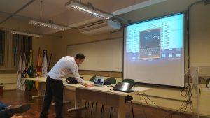 Professor Avelino Zorzo falando ao microfone, mexendo em seu computador, enquanto projeta um simulador da máquina de criptografia chamada Enigma