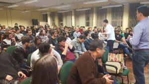 Professor Avelino Zorzo falando ao microfone, respondendo perguntas da plateia, com o professor Elder Rodrigues próximo a ele