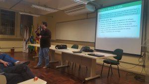 Professor João Pablo falando ao microfone com uma projeção ao fundo com título 'Objetivos e Metas do LESA'