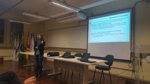 Professora Aline Mello palestrando em frente a uma projeção com o título 'Resolve e Avalia!'