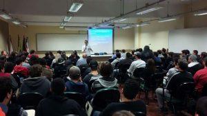 Professor Avelino Zorzo falando ao microfone para a plateia de alunos e professores com a projeção de sua palestra ao fundo