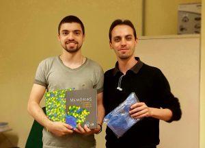 Foto de Peterson Rodrigues (aluno da Engenharia de Software sorteado) e Jean Cheiran (professor da UNIPAMPA e representante institucional da SBC) sorrindo e mostrando os brindes recebidos (livro Memórias da SBC e uma camiseta ainda embrulhada)