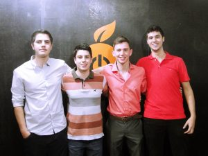 Quatro integrantes da empresa Orange abraçados na frente de um painel com o logotipo da empresa (uma laranja estilizada com o botão ligar/desligar no centro)